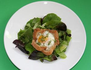 Toastnester mit Ei auf Blattsalat