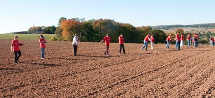 Kinder säen auf dem Feld.