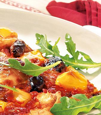 Kartoffelpizza mit schwarzen Oliven, Mozzarella und Rucola