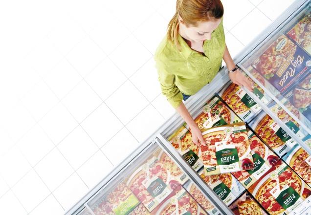 Frau vor Tiefkühlung greift nach einer Pizza