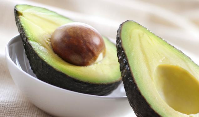 zwei Avocado Hälften mit Kern in einer Schüssel