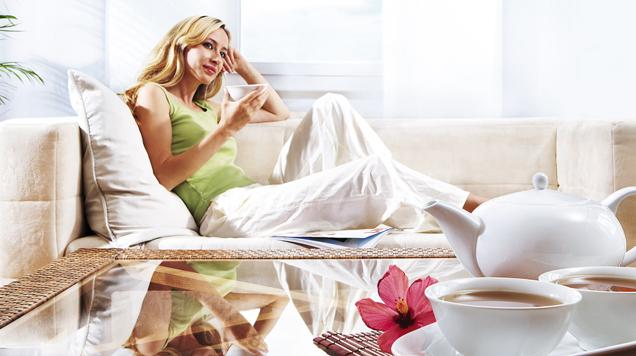 Frau liegt auf Sofa und trinkt Tee