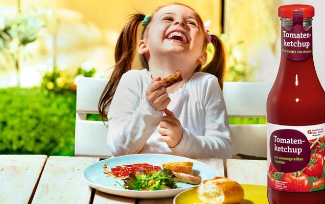 Mädchen isst Wurst mit Ketchup