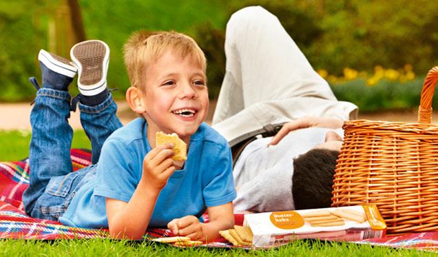 Kind liegt mit Butterkeks auf einer Wiese