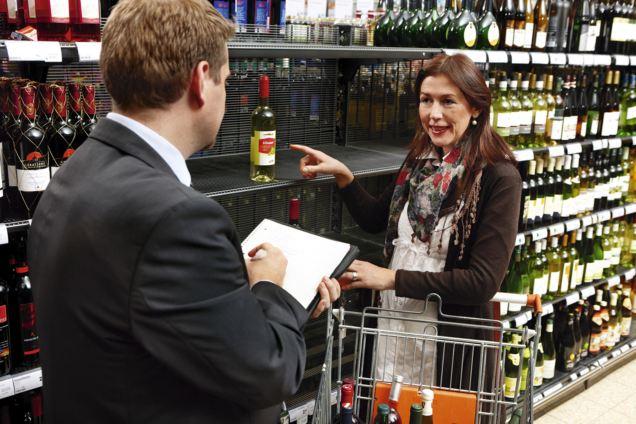 Zwei Mitglieder des Kundenrats vor einem Weinregal