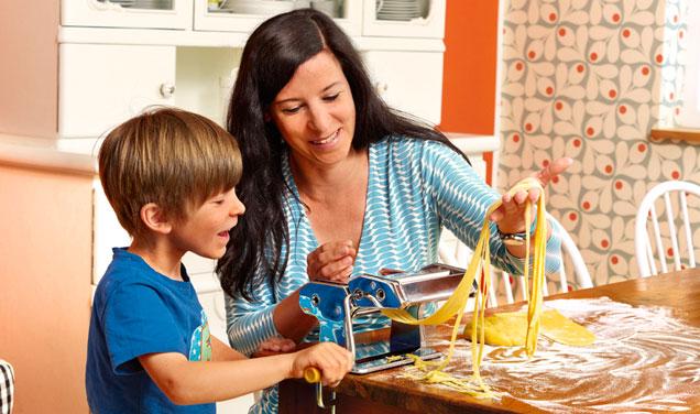 Mutter und Kind machen Nudeln mit Nudelmaschine