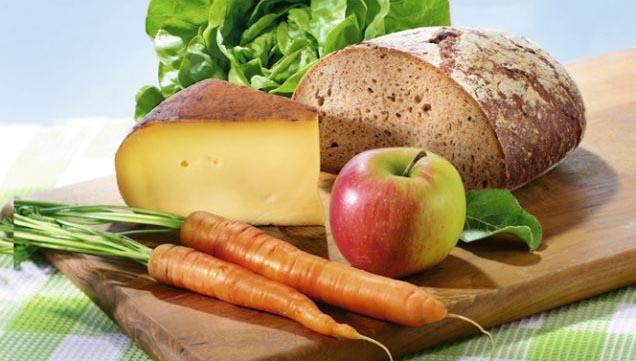 Regionale Lebensmittel auf einem Holzbrett, Brot, Möhren, Käse, Apfel und Salat.