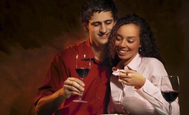 Paar, das isst und Wein trinkt