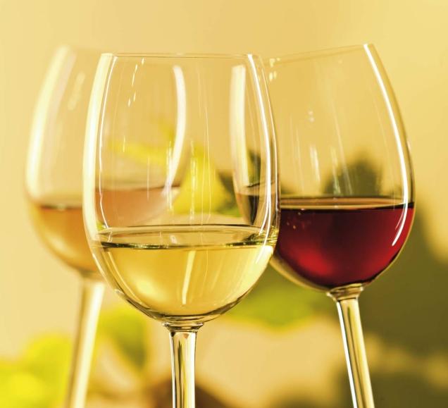 Drei Gläser mit Rot- und Weißwein vor sanftem gelbem Hintergrund
