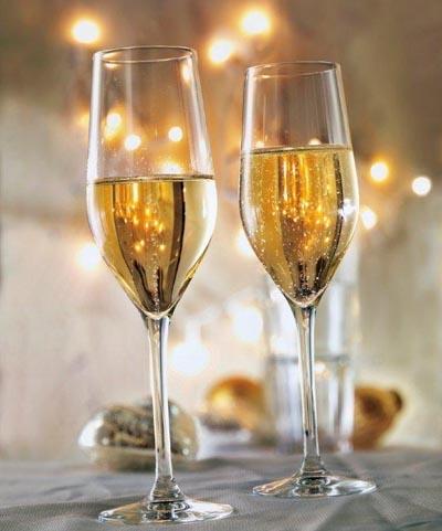 Zwei gefüllte Champagnergläser auf festlich gedecktem Tisch